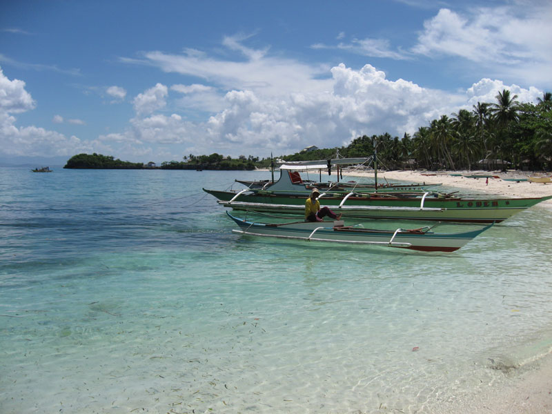 Guimbitayan.fisherman.on.boat.northern.beach.jpg