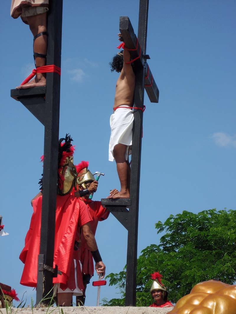 Thefeet being nailed to the cross with a hammer