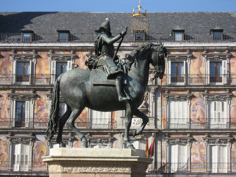 Statue of King Philip III and its fabulously painted bright red facades of Plaza Major in the back